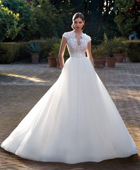 In questa foto una modella indossa un abito da sposa con scollatura Queen Anne di Valerio Luna