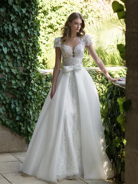 In questa foto una modella indossa un abito da sposa con scollatura Queen Anne di Nadia Orlando
