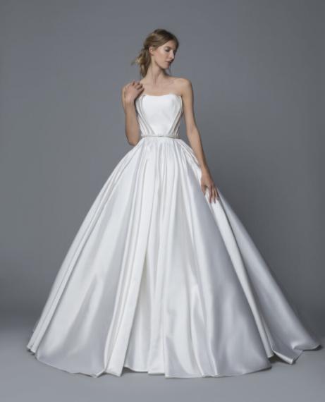 In questa foto una modella indossa un abito da sposa redingote in mikado di seta di Antonio Riva