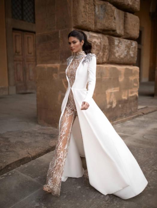 In questa foto una modella indossa un abito da sposa invernale con tuta elegante e giacca lunga