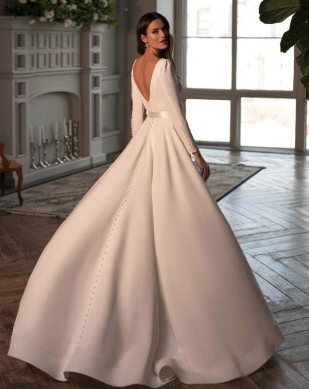 In questa foto una modella indossa un abito da sposa invernale con maniche lunghe