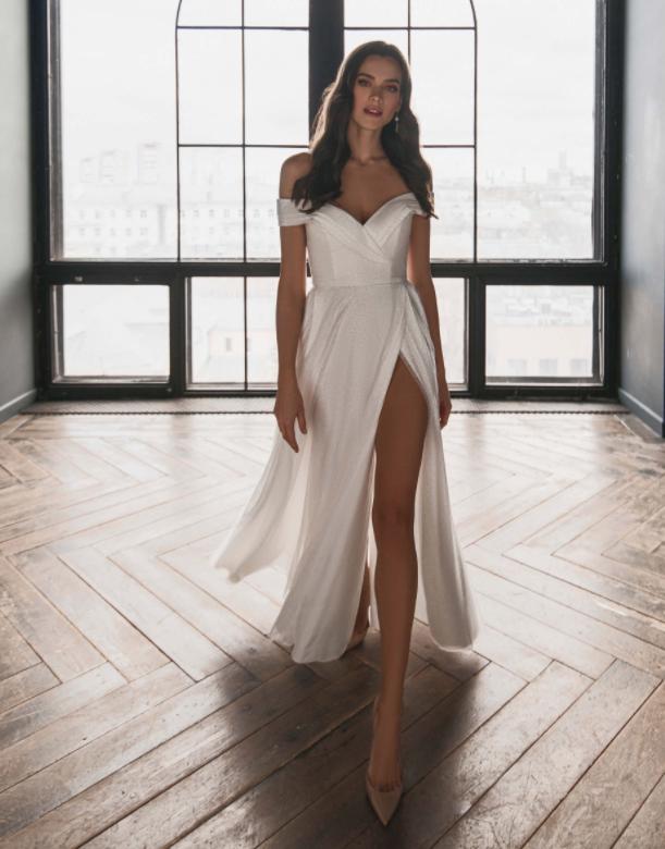 In questa foto una modella indossa un abito da sposa con profondo spacco adatto per un matrimonio estivo