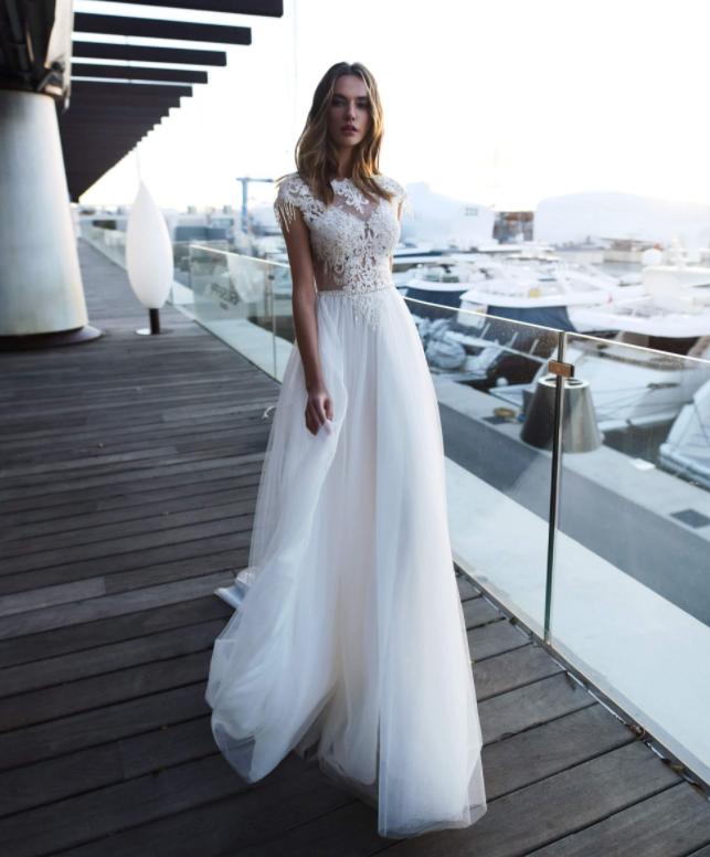 In questa foto una modella indossa un abito da sposa scivolato con mezze maniche, adatto per un matrimonio in primavera