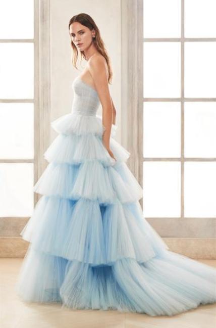 In questa foto una modella indossa un abito da sposa celeste, di tulle a balze, firmato Oscar de la Renta
