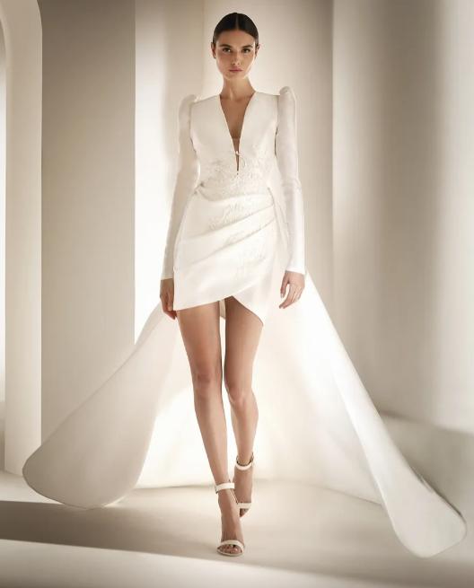 In questa foto una modella indossa un abito da sposa corto davanti e con strascico dietro di Atelier Pronovias