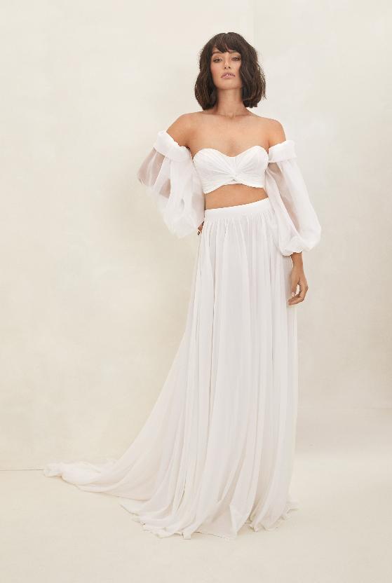 In questa foto una modella indossa un abito da sposa con maniche a palloncino di Flora Bridal 2021