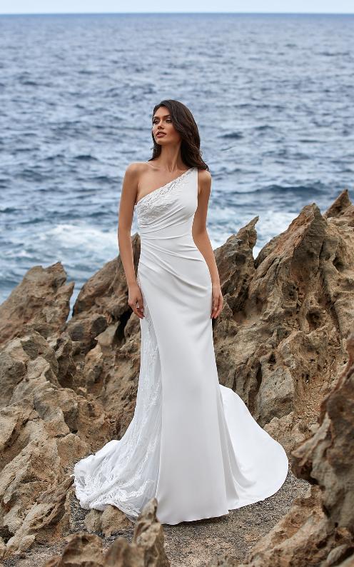 In questa foto una modella indossa un abito da sposa monospalla della collezione Pronovias 2021