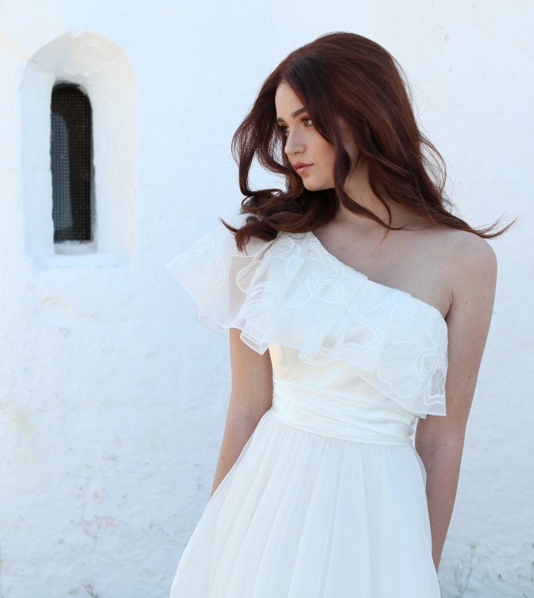 In questa foto una modella indossa un abito da sposa monospalla della collezione Valentini 2021