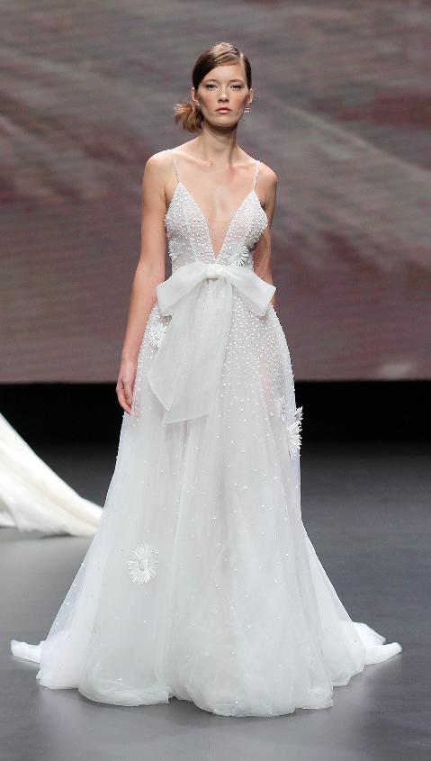 In questa foto una modella indossa un abito da sposa con scollo a V di Leonie Bridal 2021