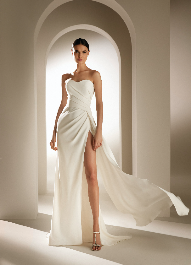 In questa foto una modella indossa un abito da sposa con profondo spacco della linea Atelier Pronovias 2021