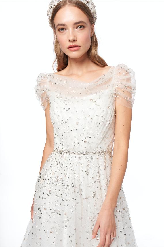In questa foto una modella indossa un abito da sposa bianco con micro e maxi paillettes argento di Jenny Packham 2021