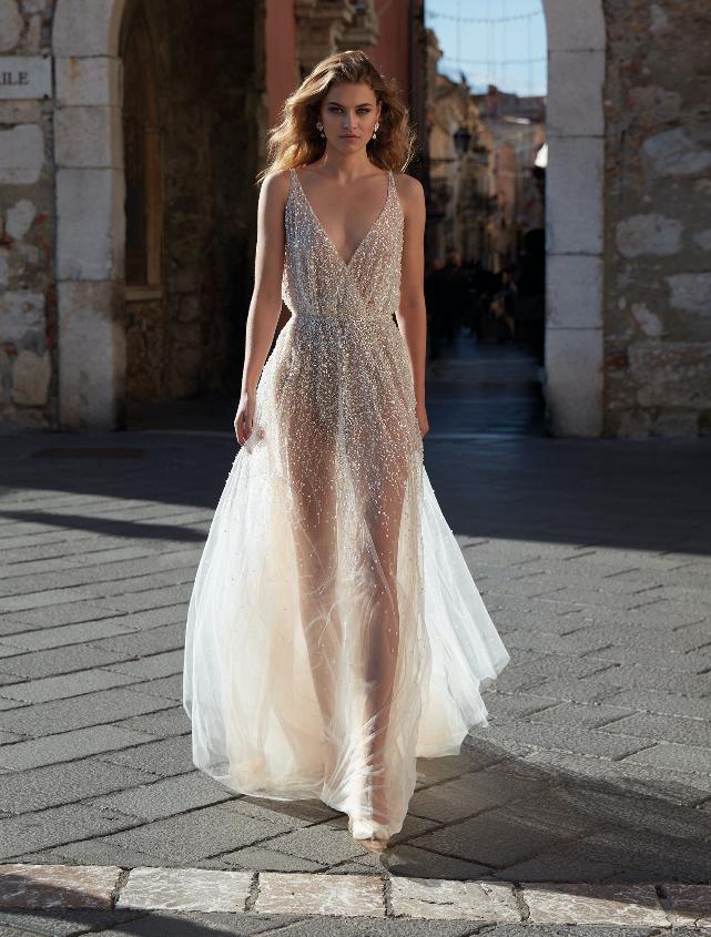 In questa foto una modella indossa un abito da sposa sparkling della collezione Nicole Milano 2021