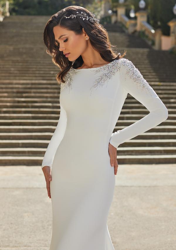 In questa foto una modella indossa un abito da sposa minimal di Pronovias 2021 impreziosito da dettagli sparkling e Swarovski sulle spalle e sullo scollo omerale