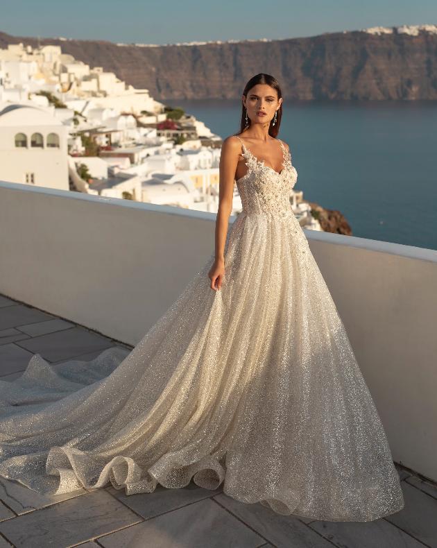 In questa foto una modella indossa un abito ampio e in tessuto luminoso della linea Ricca Spose 2021