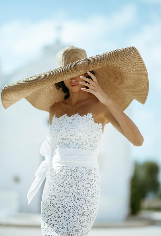 In questa foto una modella indossa un cappello in paglia dal diametro circolare grandissimo e un abito da sposa in pizzo di Luisa Sposa 2020/2021