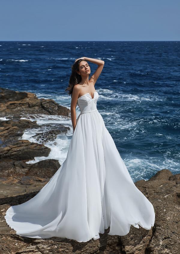 In questa foto una modella in riva al mare indossa un abito da sposa bianco di Pronovias 2021