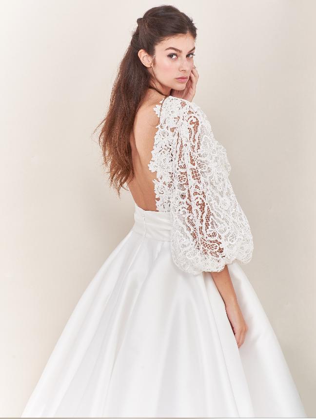 In questa foto una modella indossa un abito da sposa con maniche in pizzo oversize della collezione Tosca Spose 2021