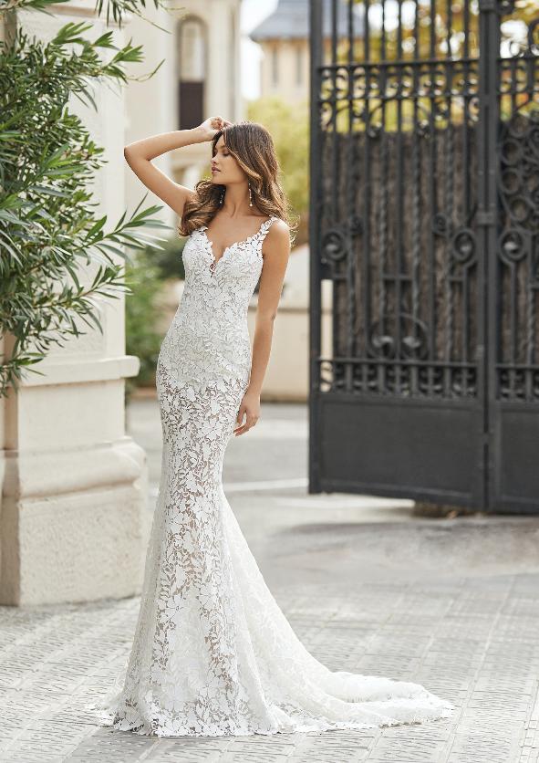 In questa foto una modella con un abito da sposa in pizzo all over di Rosa Clarà 2021