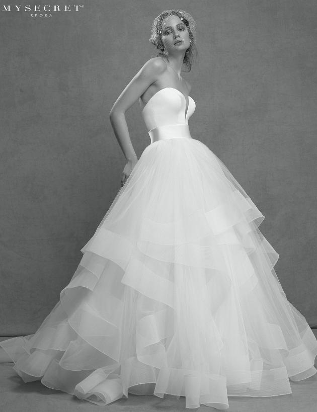 In questa foto una modella indossa un vaporoso abito da sposa in tulle firmato My Secret Sposa 2021