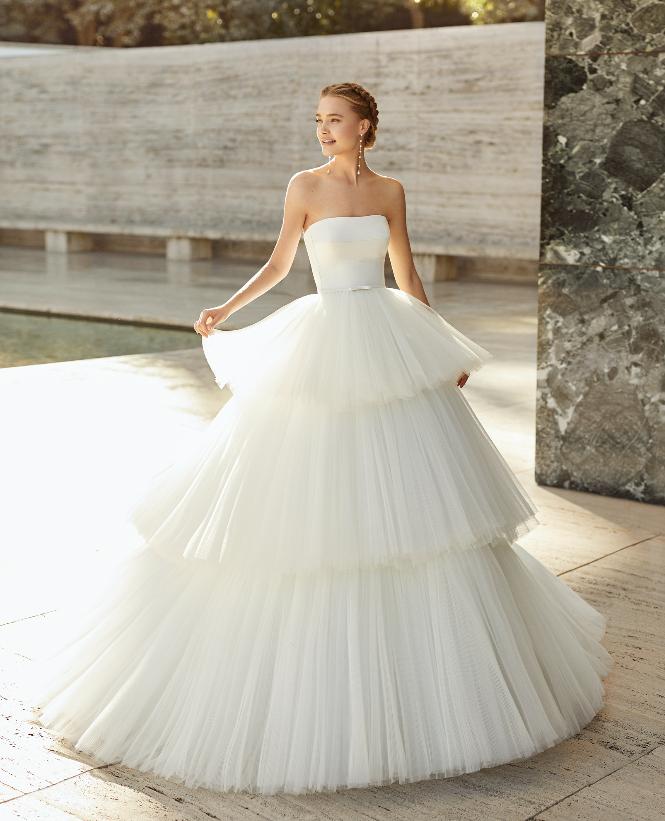 In questa foto una modella indossa un abito a balze in tulle della collezione sposa Rosa Clarà 2021