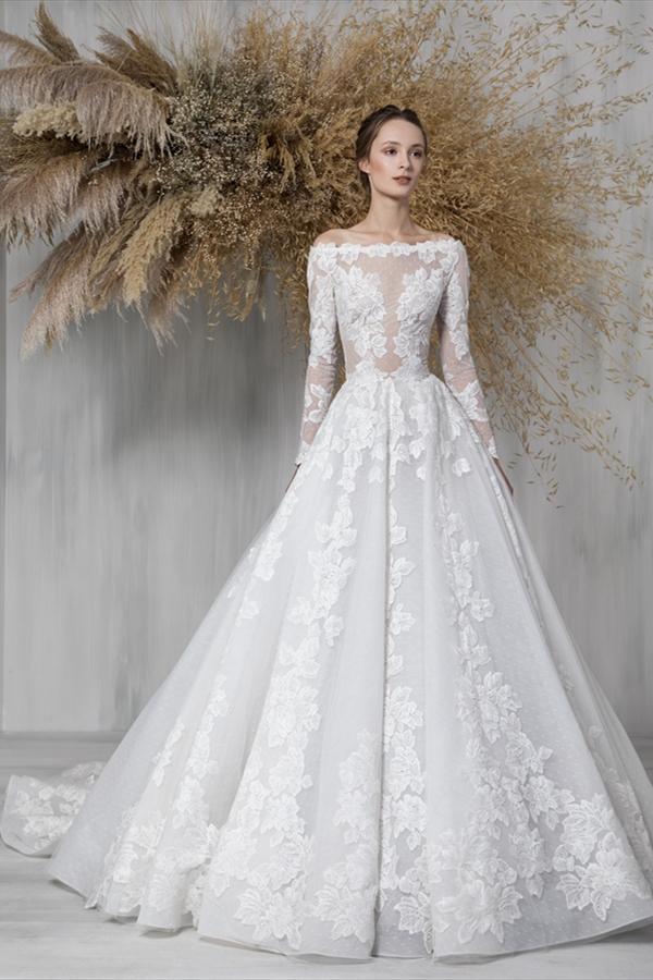 In questa foto una modella indossa un abito da sposa con maniche lunghe e scollo omerale, perfetto per nozze in autunno
