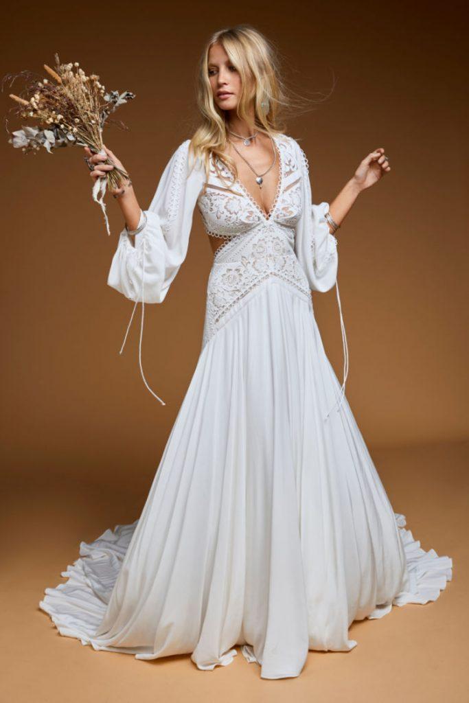 In questa foto una modella indossa un abito da sposa leggero e scivolato, con maniche lunghe e morbide, perfetto per un matrimonio in autunno