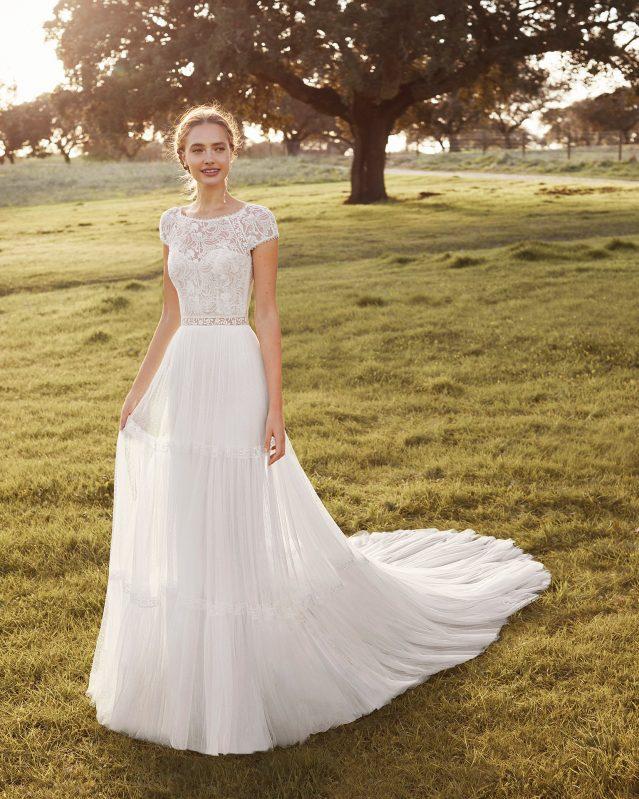 In questa foto una modella indossa un abito da sposa boho chic di Rosa Clarà