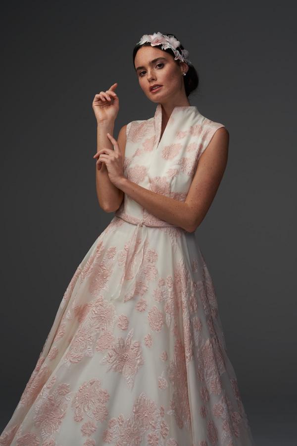 In questa foto una modella indossa un abito da sposa broccato nei toni del rosa firmato Chiara Vitale Bridal