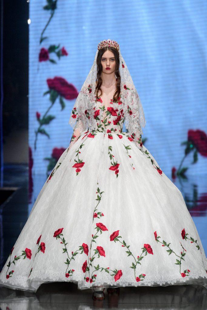 In questa foto una modella indossa un abito da sposa principesco con ricami di rose rosse firmato da Amelia Casablanca