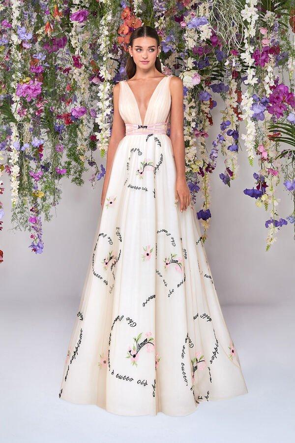In questa foto una modella indossa un abito da sposa con disegni e frasi stampati di Atelier Emé