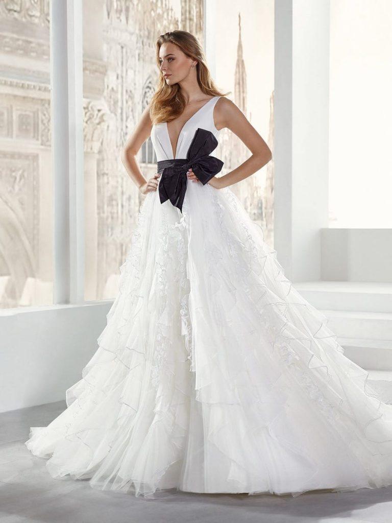 In questa foto una modella indossa un abito da sposa con fiocco nero sotto il seno di Nicole