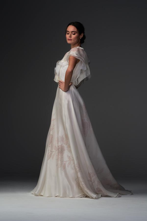 In questa foto una modella indossa un abito da sposa con fiori rosa dipinti a mano di Chiara Vitale Bridal