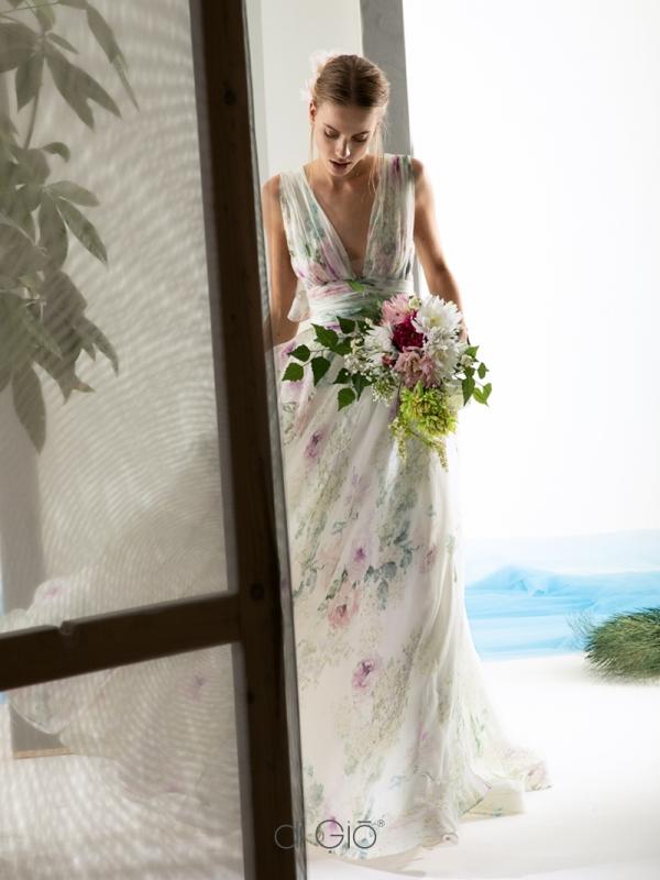 In questa foto una modella indossa un abito da sposa con disegni floreali colorati de Le Spose di Giò