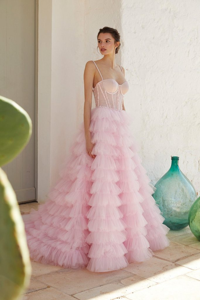 In questa foto una modella indossa un abito da sposa rosa in tulle a balze di Blumarine Sposa