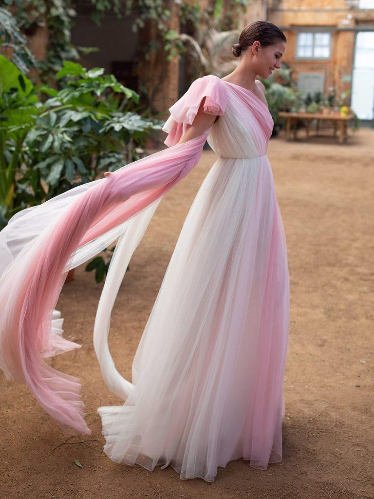 In questa foto una modella indossa un abito da sposa rosa degradè di White One Bridal