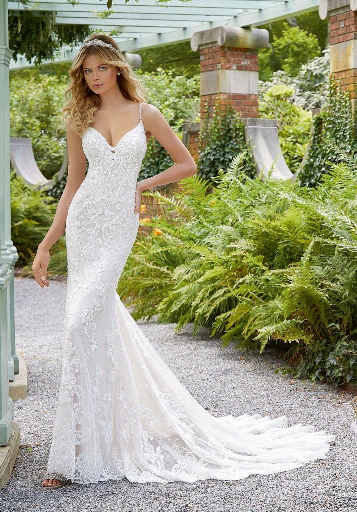In questa foto una modella indossa un abito da sposa con bretelle super sottili di Madeline Gardner New York