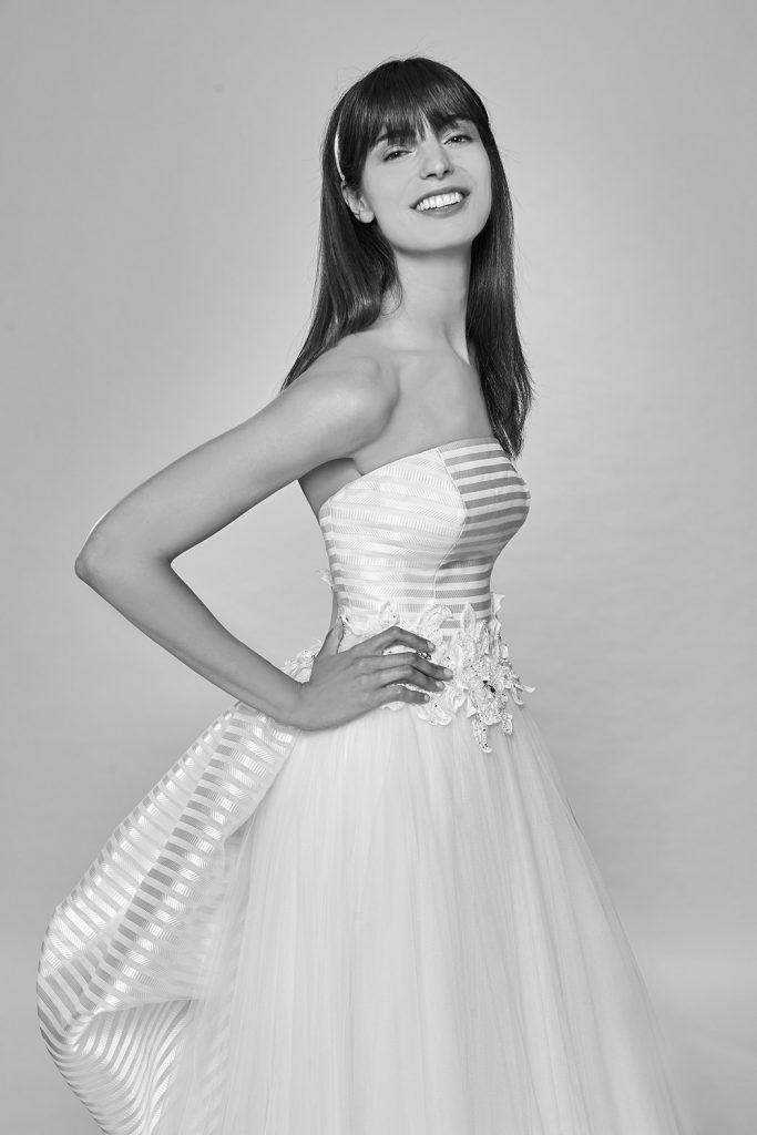 In questa foto una modella indossa un abito da sposa con scollatura dritta di Bellantuono