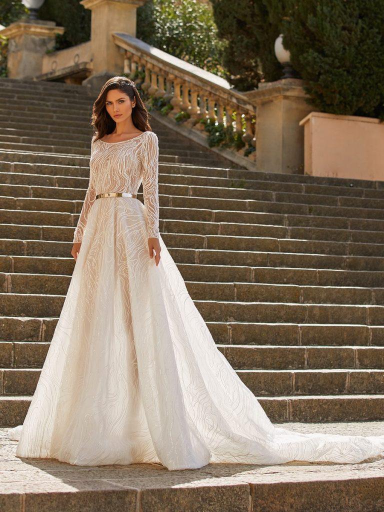 In questa foto una modella indossa un abito da sposa con scollatura rotonda di Pronovias