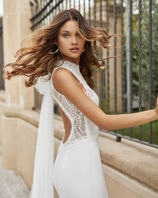 In questa foto una modella indossa un abito da sposa con scollatura all'americana di Rosa Clarà