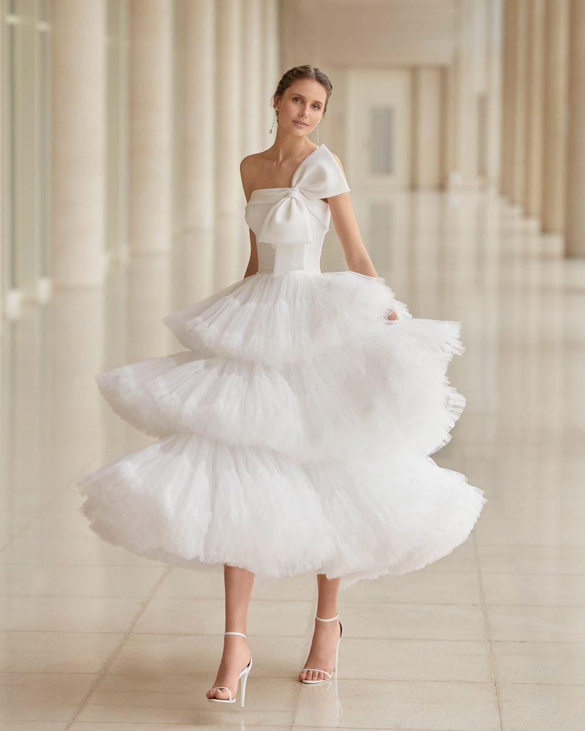 In questa foto una modella indossa un abito da sposa a balze di Aire Barcelona