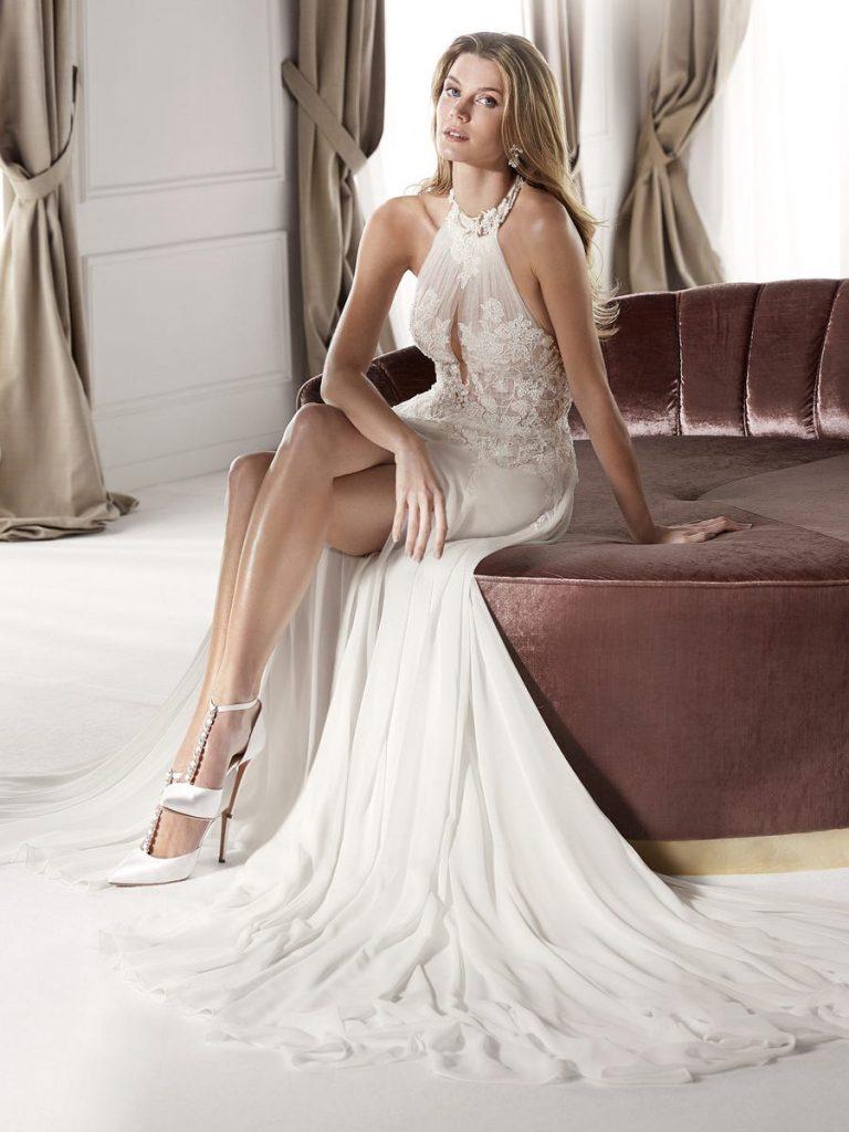 In questa foto una modella indossa un abito da sposa corto con strascico di Nicole