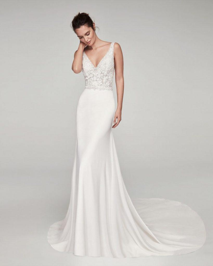 In questa foto una modella indossa un abito da sposa in crêpe georgette di Alma Novia