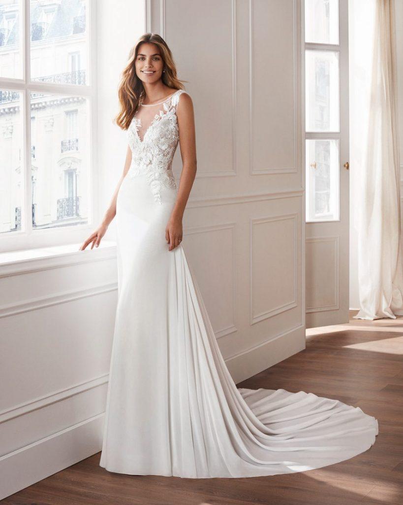 In questa foto una modella indossa un abito da sposa in crêpe georgette di Valerio Luna