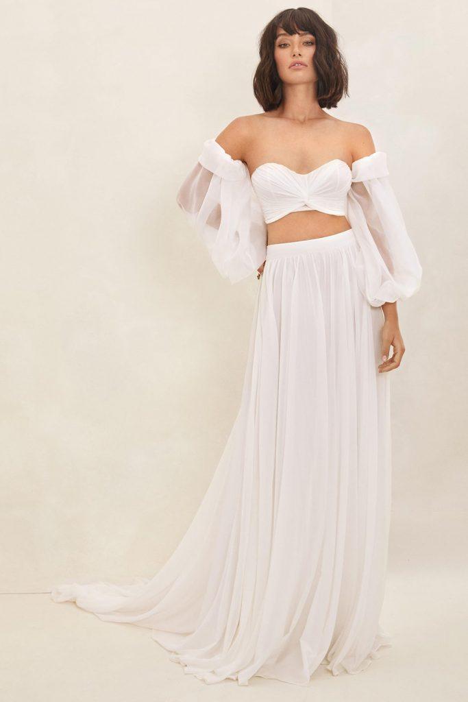 In questa foto una modella indossa un abito da sposa crop top perfetto per un matrimonio in spiaggia