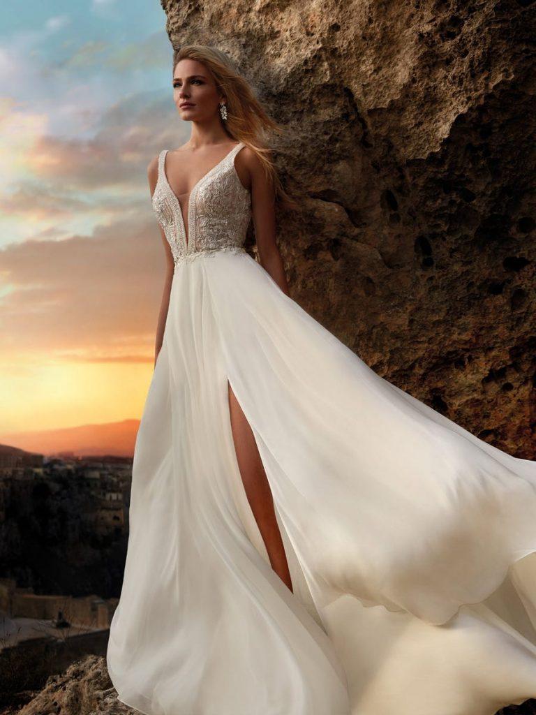 In questa foto una modella indossa un abito da sposa con profondo scollo a V e spacco perfetto per un matrimonio in estate