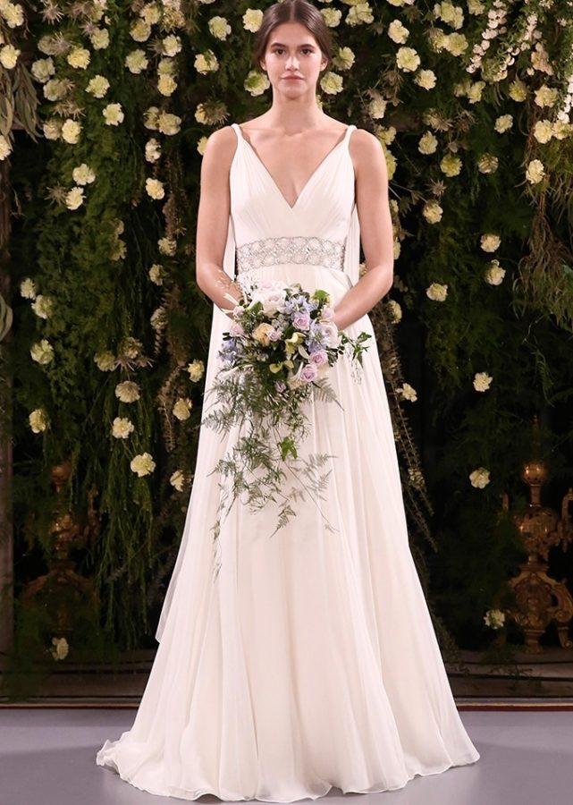 In questa foto una modella indossa un abito da sposa in stile impero, ottimo per una donna dal fisico a mela