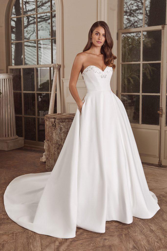 In questa foto una modella indossa un abito da sposa modello redingote perfetto per un fisico a pera