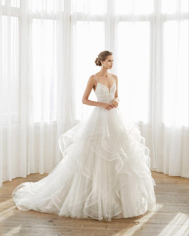 In questa foto una modella indossa un abito da sposa con ruches sulla gonna, perfetto per le donne con il fisico a rettangolo