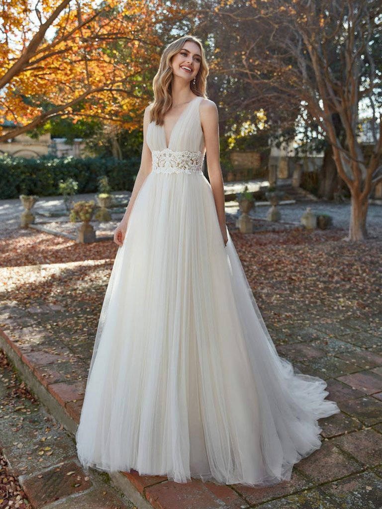 In questa foto una modella indossa un abito da sposa stile impero della collezione Studio San Patrick