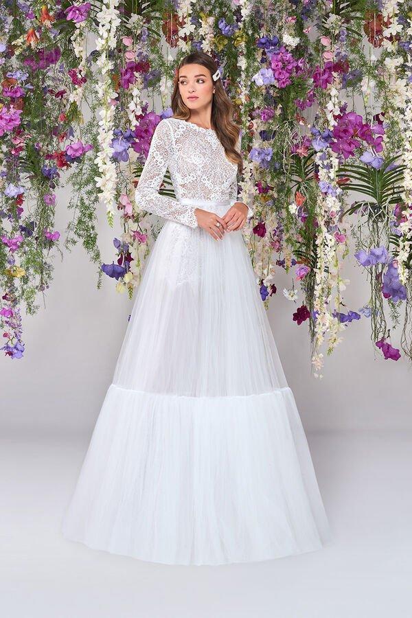 In questa foto una modella indossa un abito da sposa con maniche lunghe perfetto per un matrimonio in inverno